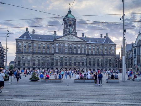 Amsterdam, Netherlands - July 18, 2018: The Royal Palace at Dam square at dusk in Amsterdam. Dam square has become a very popular tourist destination. Editorial
