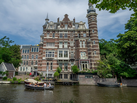 Amsterdam, Netherlands - July, 2018: Scenes along beautiful and historic canals in the heart of Amsterdam. Buildings on the canal are a form of traditional Dutch architecture which is now very popular.