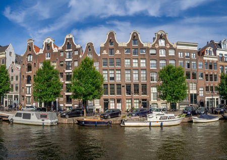 Amsterdam, Netherlands - July, 2018: Dutch buildings, boats and cultural life along the canals in the heart of the Netherlands beautiful capital city of Amsterdam.