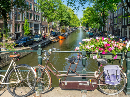 Amsterdam, Netherlands - July 22, 2018: Old bicycles along a bridge over a canal in Amsterdam. There are bikes locked up on many canals as it is a popular mode of transportation here. Editorial