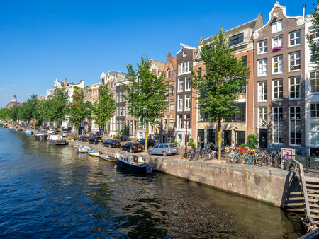 Amsterdam, Netherlands - July 22, 2018: Buildings and boats along the Singel Canal in the centre of Amsterdam. The canals of Amsterdam are famous tourist destinations.