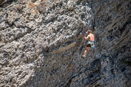 Rock climbers climbing a rock face at Grassi Lakes outside Canmore in Kananaskis Country.