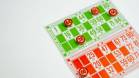 Board game of lotto or bingo. Wooden barrels with game cards on a white isolated background. The concept of sitting at home. Archivio Fotografico