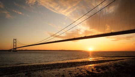 Sun setting below the Humber Bridge, East Riding of Yorkshire Stock Photo