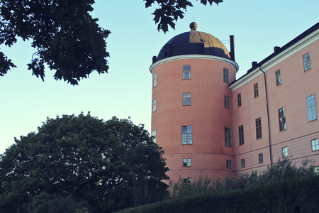 season specific: Beautiful summer season specific photograph. An old castle in Uppsala, Sweden. Great colors and beautiful blue sky.