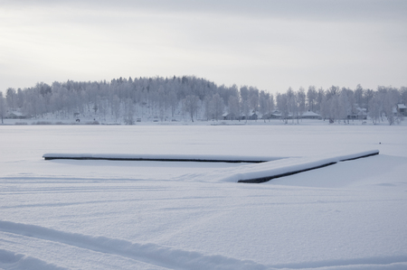 Beautiful winter specific photo. Frozen lake at wintertime. Photo with beautiful forest in the background and a dock lying in the middle of the lake.