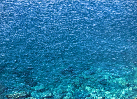Crystal clear blue ocean water. Close up shot with very nice lights and coral showing beneath the surface. Mediterranean environment.