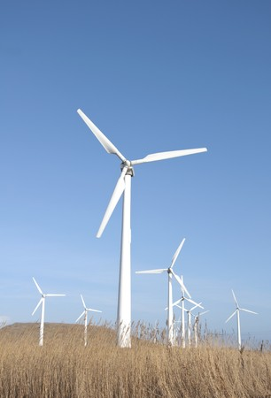 Wind turbines against blue sky background photo