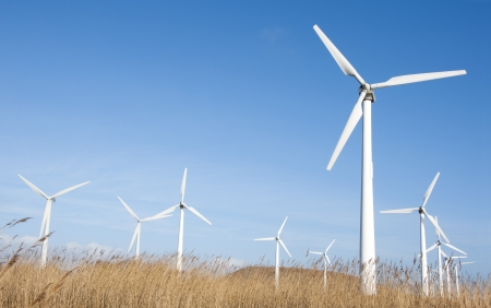 energy fields: wind turbine farm against blue sky background  Stock Photo