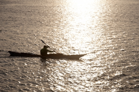Silhouette of a man kayaking in the lake at sunset  photo