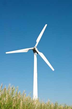 Single white wind turbine on blue sky background photo