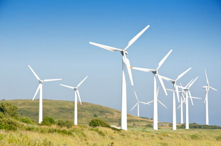 groene weide met windturbines die elektriciteit produceert Stockfoto