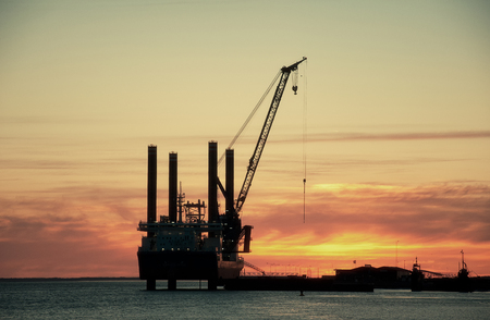 crane: Sunset over an industry harbour with cranes Stock Photo