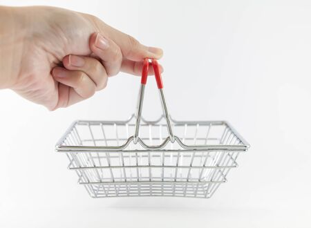 Closeup of hand holding small metallic shopping basket with red handles on white background with copy space. Concept of online shopping. Selective focus