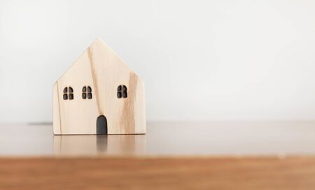 Wooden house model on wooden table with copy space. Home, housing, insurance and real estate concept.