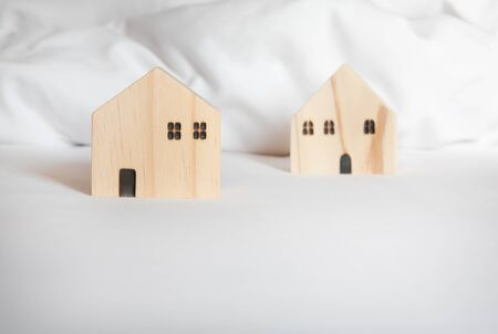 Small wooden house model on white bed. Selective focus with copy space. Home, housing, mortgage loan and real estate concept.