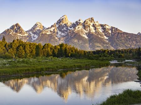 Stunning sunrise illuminating the Grand Teton Mountain Range with reflection in pond 版權商用圖片
