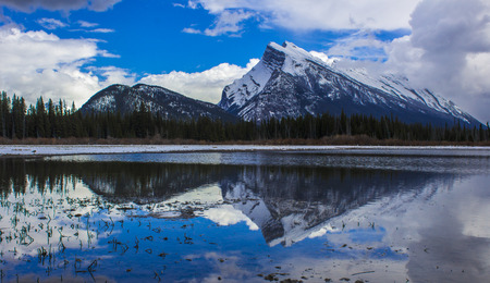 A gorgeous water reflection of a snowy mountain in the Canadian Rockies in Banff, Alberta, Canada.