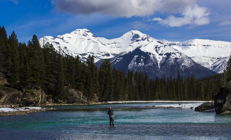 One man fishing in the aqua mountain waters of Banff in the Canadian Rockies, Canada.