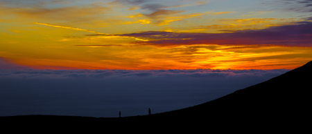 Two silhouettes at sunset above the clouds outside of San Francisco in the USA.
