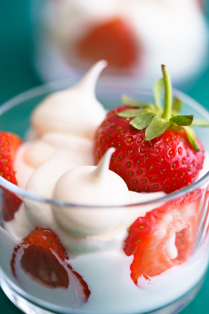 Macro shot of whipped cream, meringues and fresh strawberries in a glass bowl on a green background