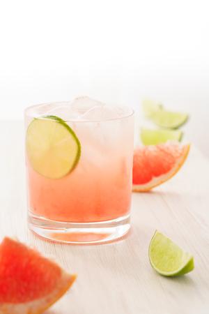 Cocktail Paloma servi avec des tranches de pamplemousse et de citron vert. Fond en bois blanc, haute résolution