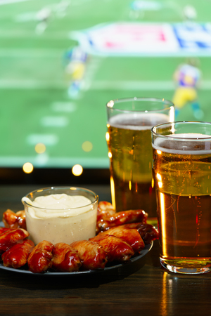 Hot barbecue chicken wings with 2 beer glasses on a dark wooden table served with honey mustard sauce. Football on a background, high resolution