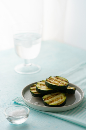 Grilled zucchini served on a white plate with a glass of water in bokeh. Blue table, high resolution 免版税图像