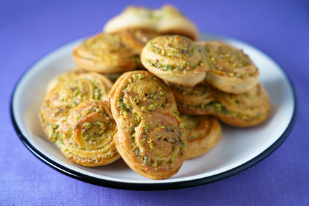 Pistachio roll buns served in a white plate with black rim. Violet linen napkin, high resolution