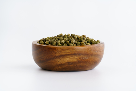 Dried green peppercorns in a wooden bowl. White background, high resolution