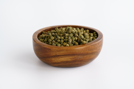 Dried green peppercorns in a wooden bowl. White background, high resolution Stock Photo - 124702040