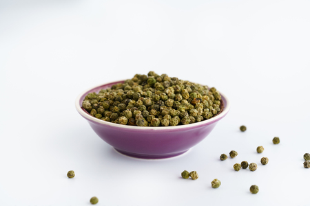 Dried green peppercorns in a violet bowl. White background, high resolution Stock Photo