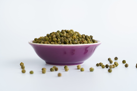 Dried green peppercorns in a violet bowl. White background, high resolution Stock Photo - 124702100