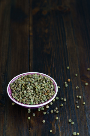 Dried green peppercorns in a violet bowl. Dark wooden table, high resolution, negative space