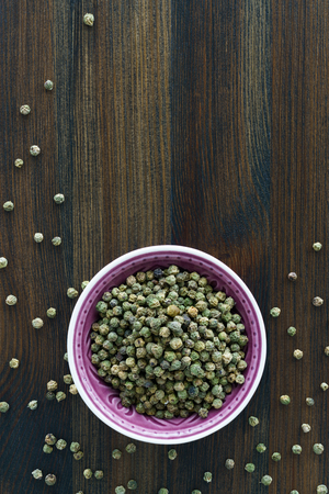 Dried green peppercorns in a violet bowl. Dark wooden table, high resolution