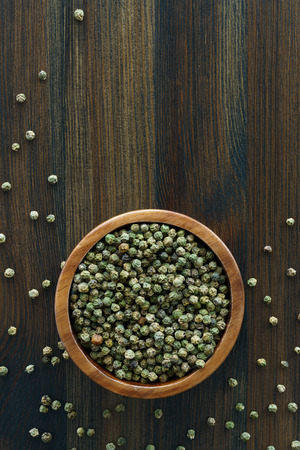 Dried green peppercorns in a wooden bowl. Dark wooden table, high resolution, negative space Stock Photo - 124704329