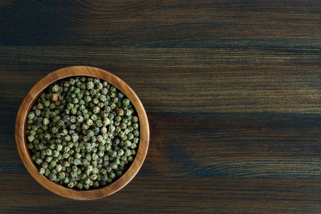 Dried green peppercorns in a wooden bowl. Dark wooden table, high resolution, negative space Stock Photo - 124704337