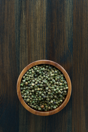 Dried green peppercorns in a wooden bowl. Dark wooden table, high resolution, negative space Stock Photo - 124704339