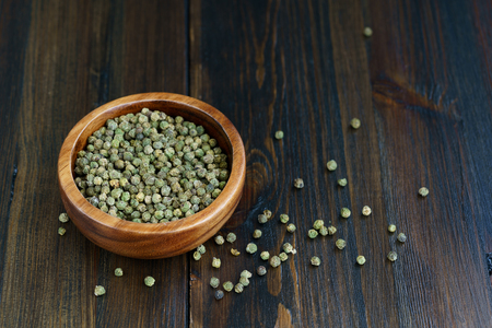 Dried green peppercorns in a wooden bowl. Dark wooden table, high resolution Stock Photo