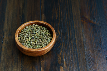Dried green peppercorns in a wooden bowl. Dark wooden table, high resolution, negative space