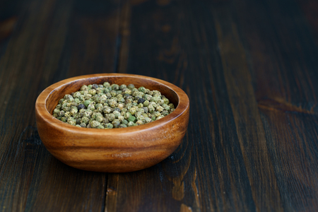 Dried green peppercorns in a wooden bowl. Dark wooden table, high resolution, negative space Stock Photo - 124704362