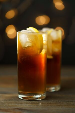 Rum and coke in a highball glass with a lemon wedge. Dark wooden table, festive lights, high resolution Archivio Fotografico