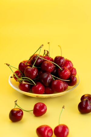 Freshly picked cherries in a glass bowl. Bright yellow background, water drops, high resolution Stockfoto