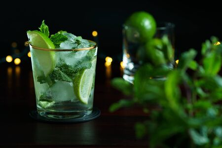 Mojito served in a glass with gold rim. Limes and mint in bokeh, dark wooden table, high resolution