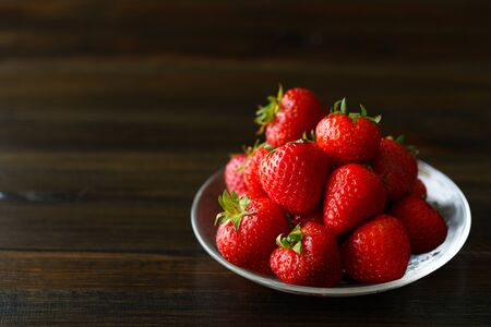 Freshly picked organic strawberries in a glass bowl. Dark wooden table, water, high resolution
