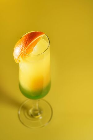 Moscow Lights cocktail in a champagne glass garnished with an orange slice. Bright yellow background, high resolution