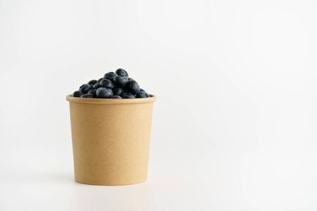 Fresh organic blueberries in a paper cup on a white background. Copy space, isolated, high resolution