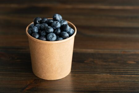 Fresh organic blueberries in a paper cup. Dark wooden table, high resolution