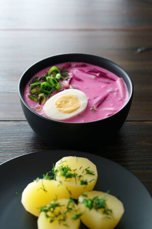 Lithuanian Saltibarsciai (Cold Beet Soup) with hard boiled egg and potatoes, seasoned with spring onions and dill. Dark wooden table, high resolution