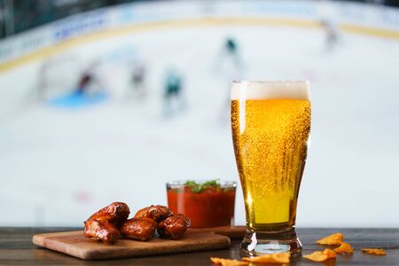 Spicy barbecue chicken wings, tomato salsa, nachos and beer on dark wooden bar table. Hockey on background, high resolution